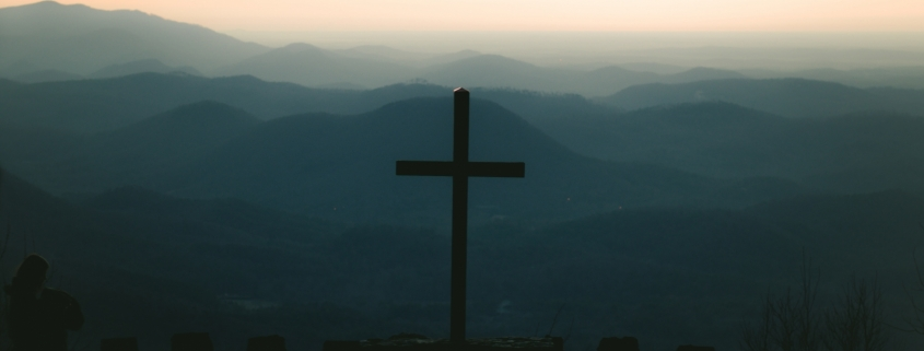 silhouette of cross on top of building during sunset
